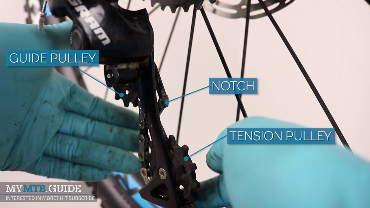 Run the chain through the rear derailleur, paying special attention to the notch, guide and tension pulley.